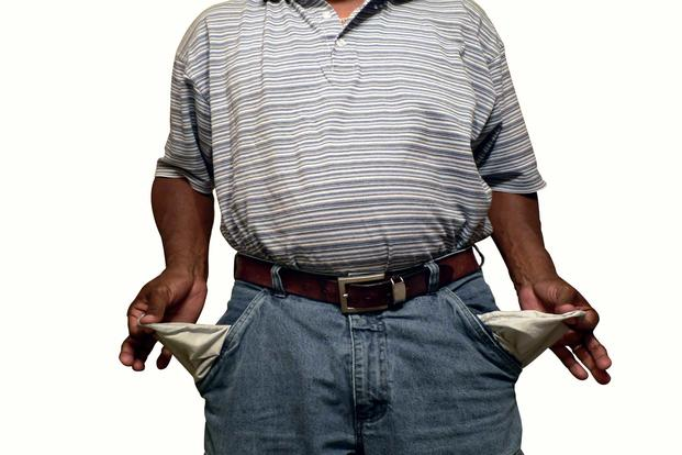 Man with empty pockets turned inside out signifying out of money