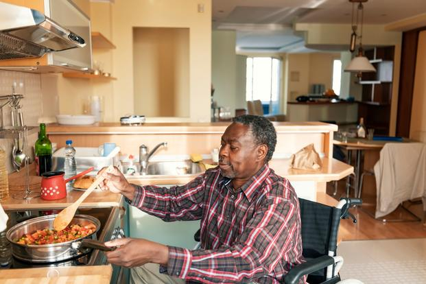 man at home cooking in wheelchair