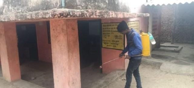 कोरोना संक्रमण से बचाव के लिए स्कूल के क्लास के बाहर सैनिटाइज करता हुआ कर्मी.