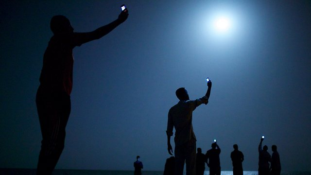 טלפון לכל אחד. תמונת השנה 2014 הגיעה מאפריקה: מהגרים בדרך לאירופה מניפים את הטלפונים הסלולריים שלהם בניסיון למצוא קליטה ולהתקשר הביתה (צילום: AFP)