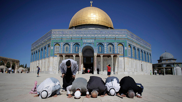 Palestinians praying outside the al-Aqsa mosque (Photo: Reuters)