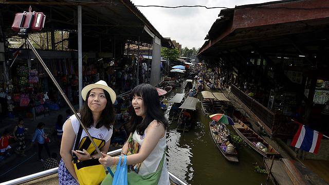 תיירות עם מקל סלפי בתאילנד, ארכיון. כדאי להיזהר (צילום: EPA)