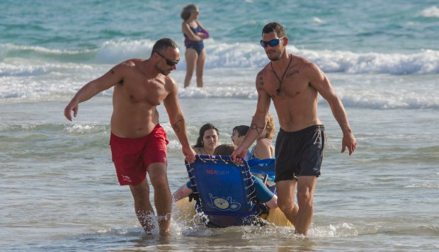 Спасатели помогают инвалиду насладиться морем. Фото: пресс-служба
