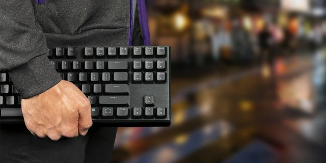 Closeup of a man carrying the MK730 keyboard by his side