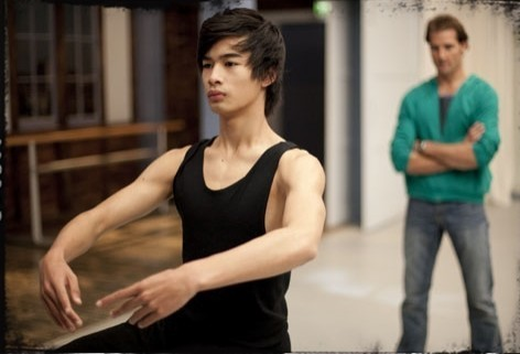 A young Asian man practices ballet, an older white man looking on from the background.