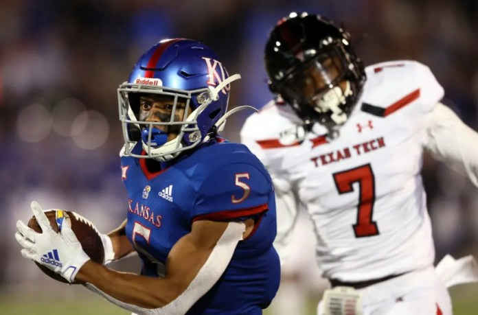 LAWRENCE, KANSAS - OCTOBER 26: Wide receiver Stephon Robinson Jr. #5 of the Kansas Jayhawks catches a pass for a touchdown as defensive back Adrian Frye #7 of the Texas Tech Red Raiders defends during the game at Memorial Stadium on October 26, 2019 in Lawrence, Kansas. (Photo by Jamie Squire/Getty Images)