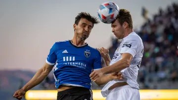 Players from the LA Galaxy and the San José Earthquakes fight a ball through the air.