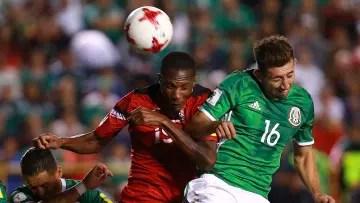 Héctor Herrera fights a ball through the air against Kevan George.