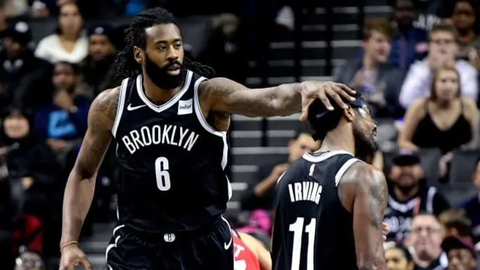 NEW YORK, NEW YORK - OCTOBER 18: Kyrie Irving #11 of the Brooklyn Nets is congratulated by his teammate DeAndre Jordan #6 after scoring a basket against the Toronto Raptors at Barclays Center on October 18, 2019 in New York, New York. (Photo by Steven Ryan/Getty Images)