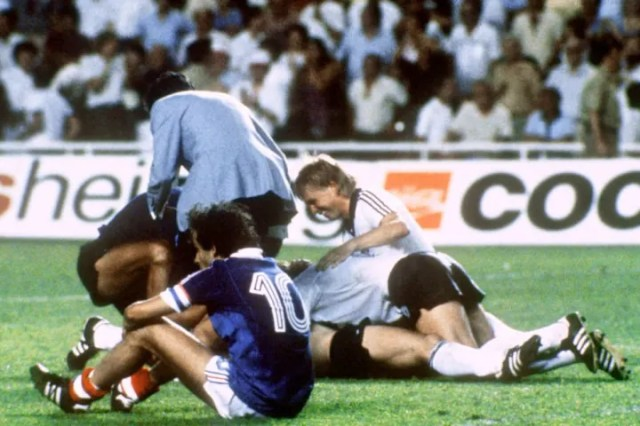 Michel Platini watches on as West Germany players celebrate