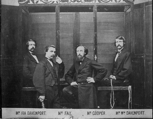 Photograph of the Davenport Brothers in front of their spirit cabinet