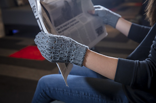 A person holding a newspaper while wearing grey fingerless gloves.