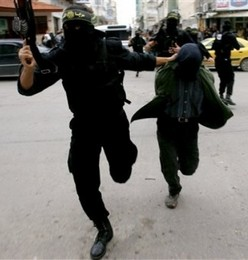 An Islamic Jihad gunman drags a suspected collaborator through the streets of Gaza.