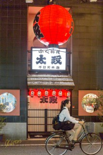 Japanese have a love for lanterns, and some of them are really big. It helps when they bike at night obviously! Girl biker passing from a restaurant in Dotonbori, Osaka.