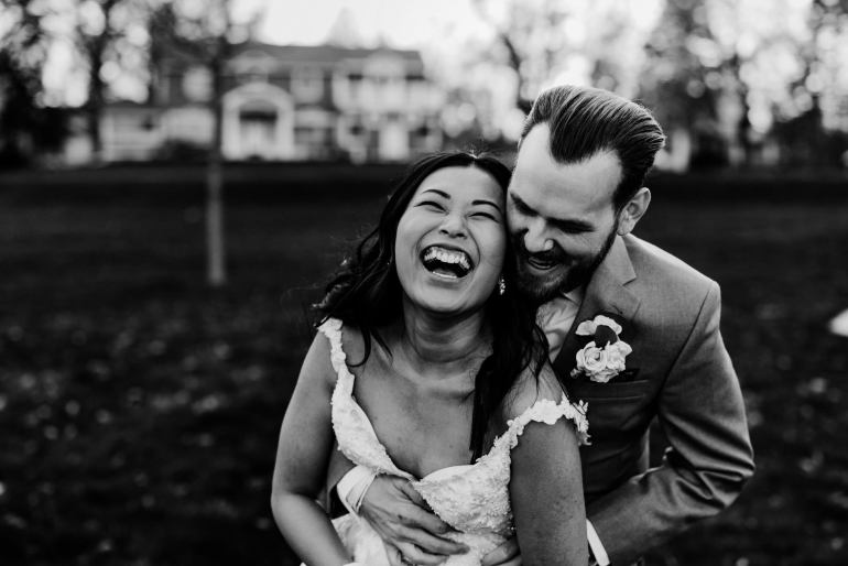Couples laughs as they hug in their wedding photos in Minneapolis