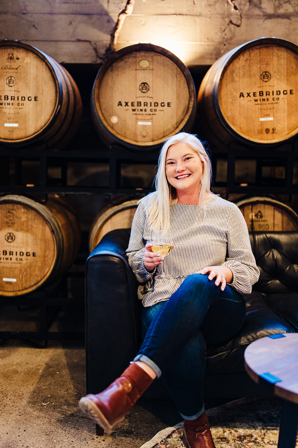 female employee smiles at camera with a glass of wine in her hand during Minnesota Urban Winery Branding