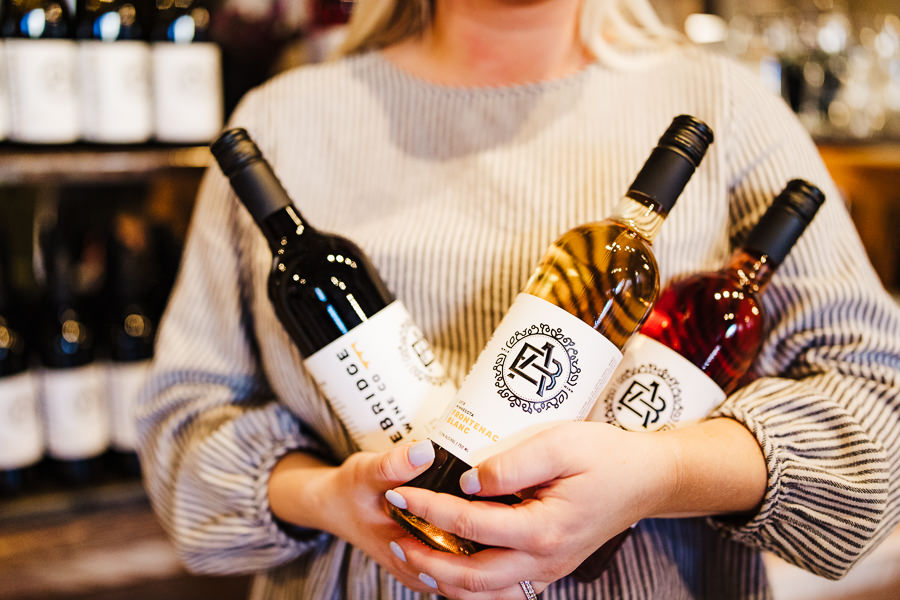 woman holds three bottles of wine during Minnesota Urban Winery Branding session