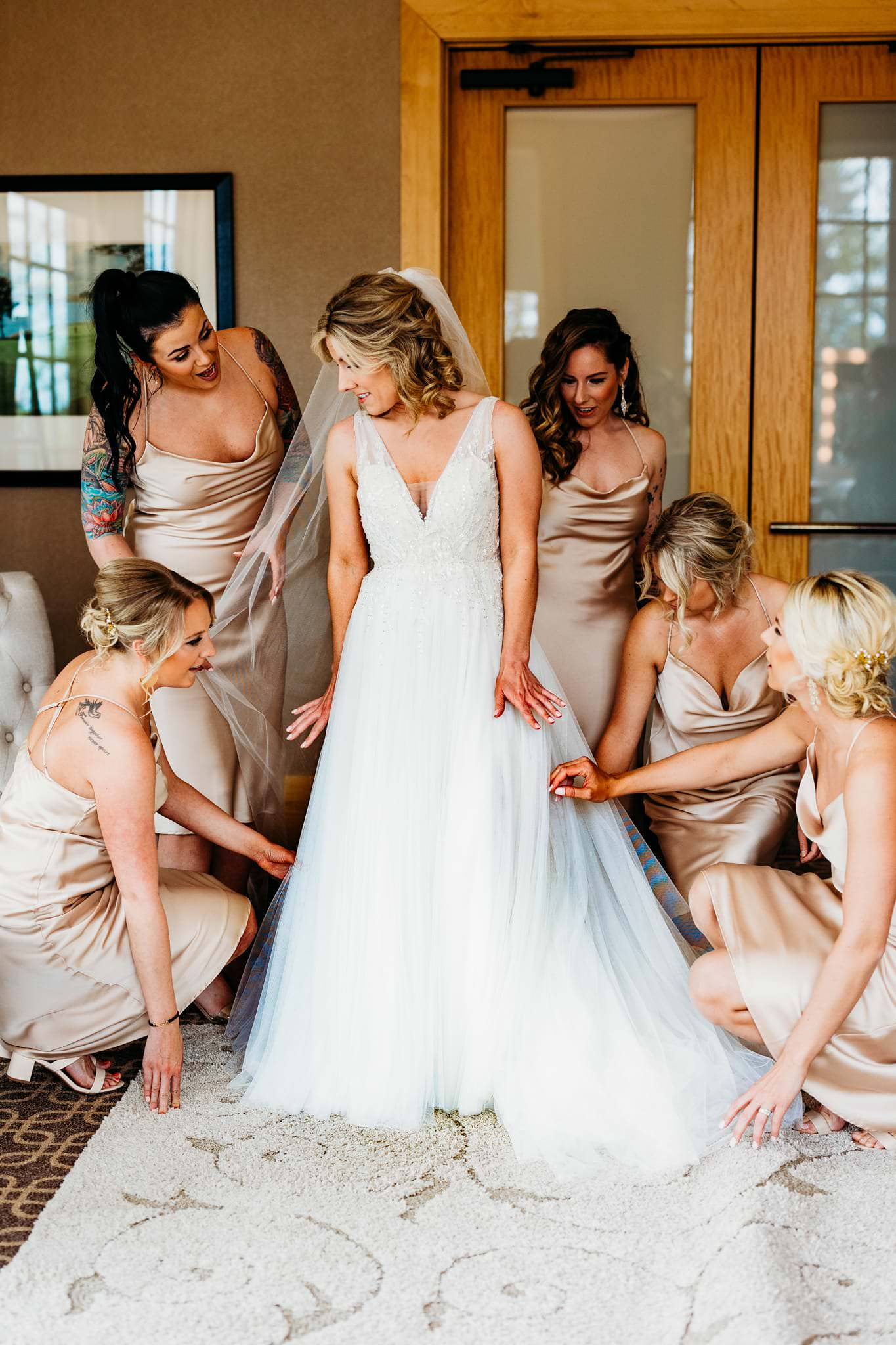bridesmaids help bride get ready during in the dressing room at her hazeltine national golf club wedding