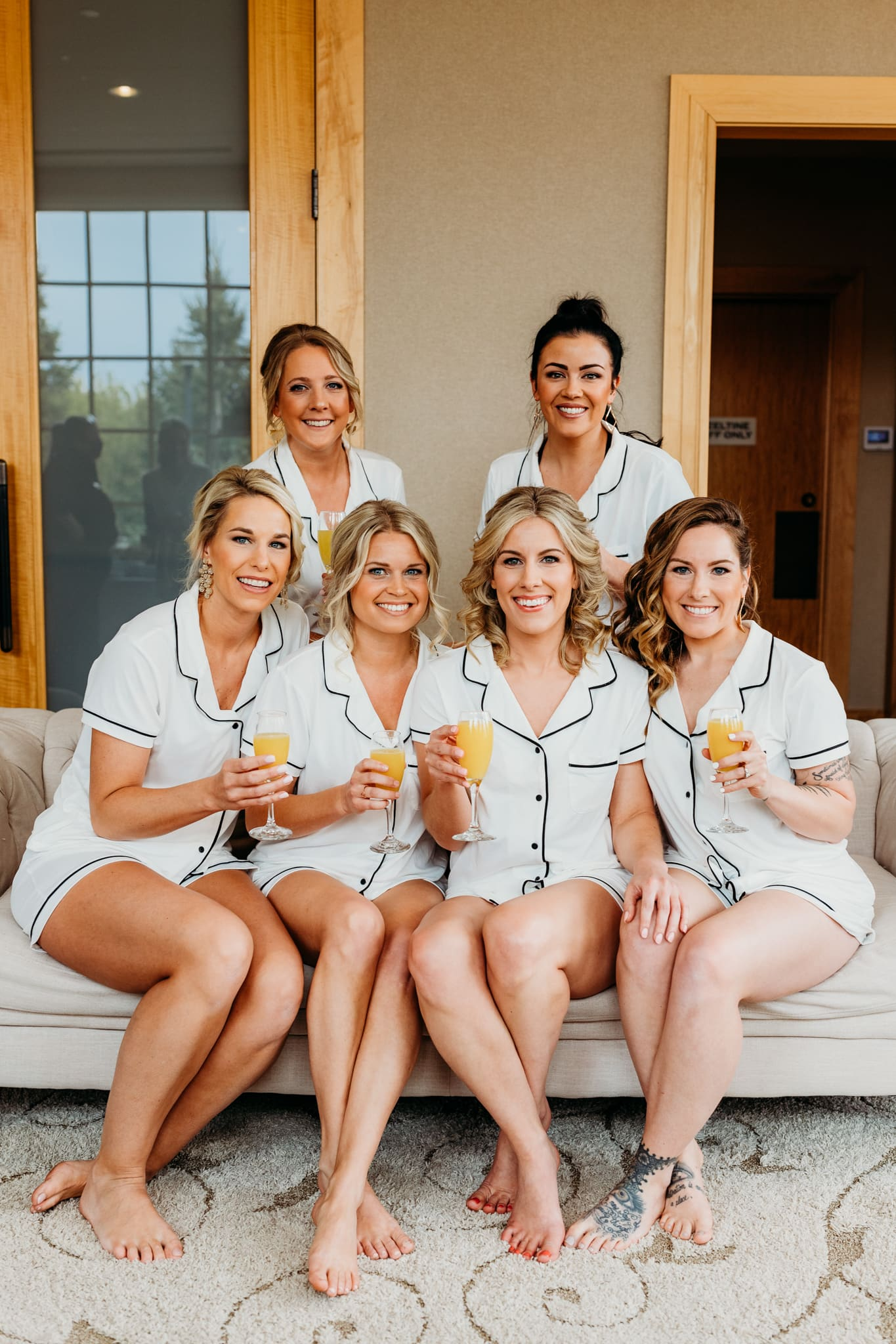 bride and bridesmaids smile while they hold mimosas as they get ready for a hazeltine national golf club wedding