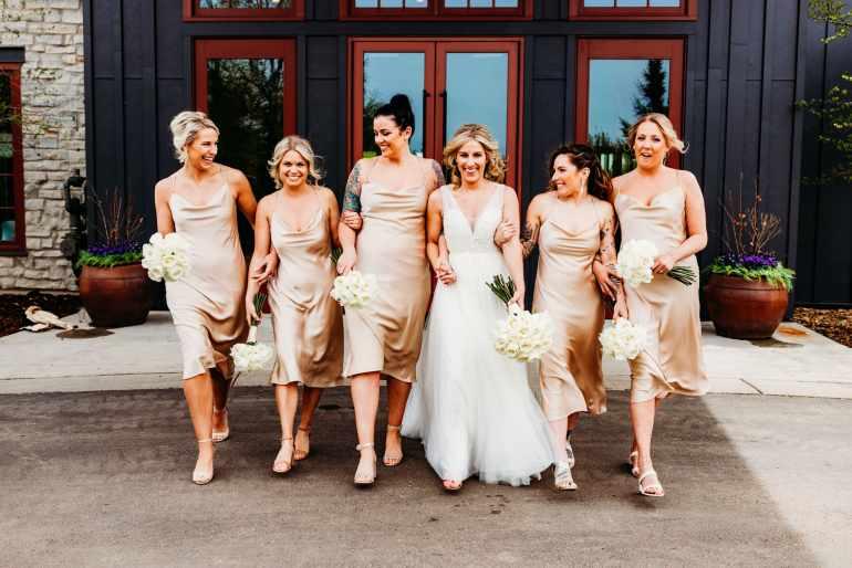Bride walks outside at herHazeltine National Golf Club wedding with her bridesmaids