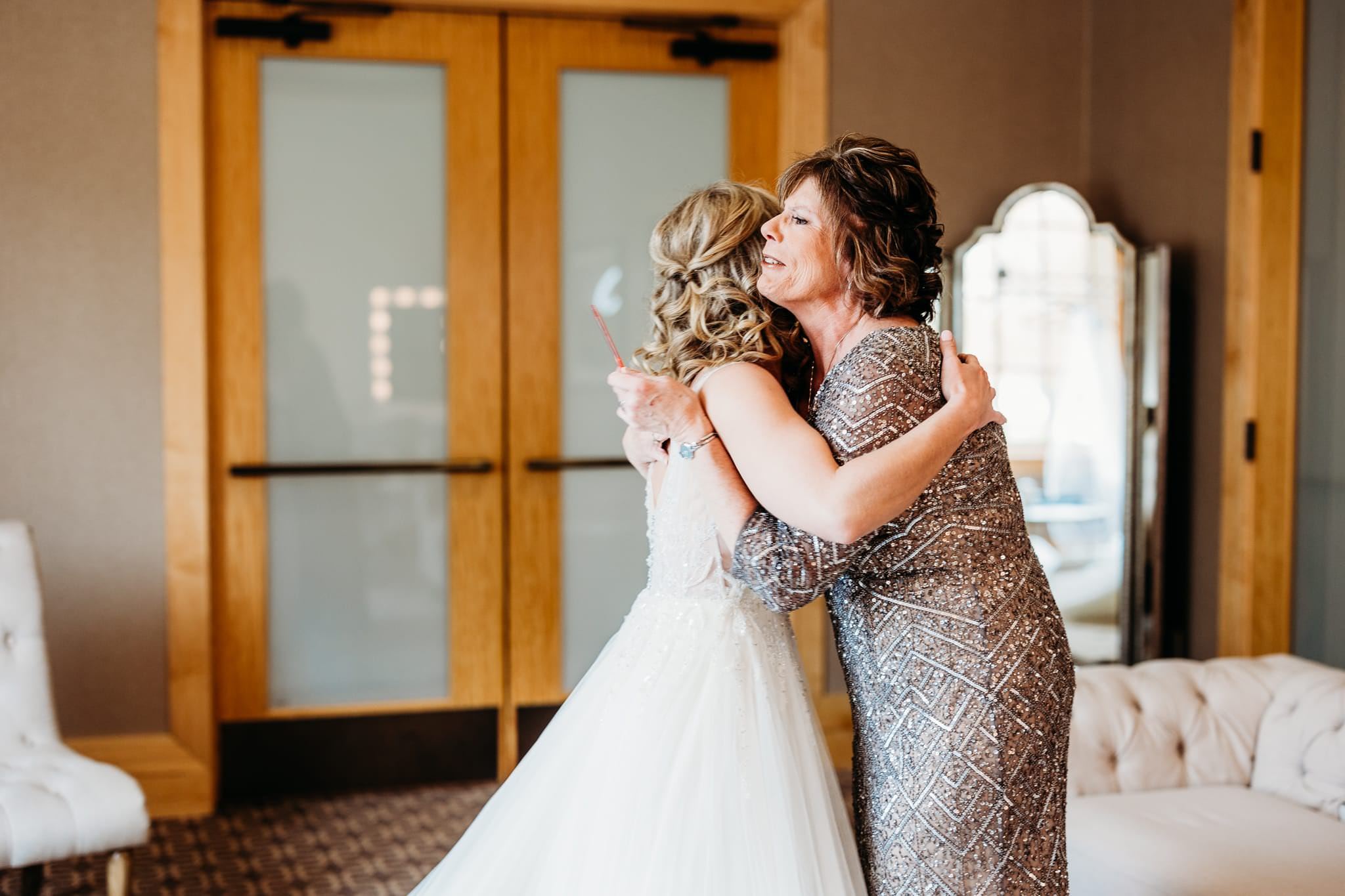 mother of the groom tears up when she sees the bride in her dress before their hazeltine national golf club wedding