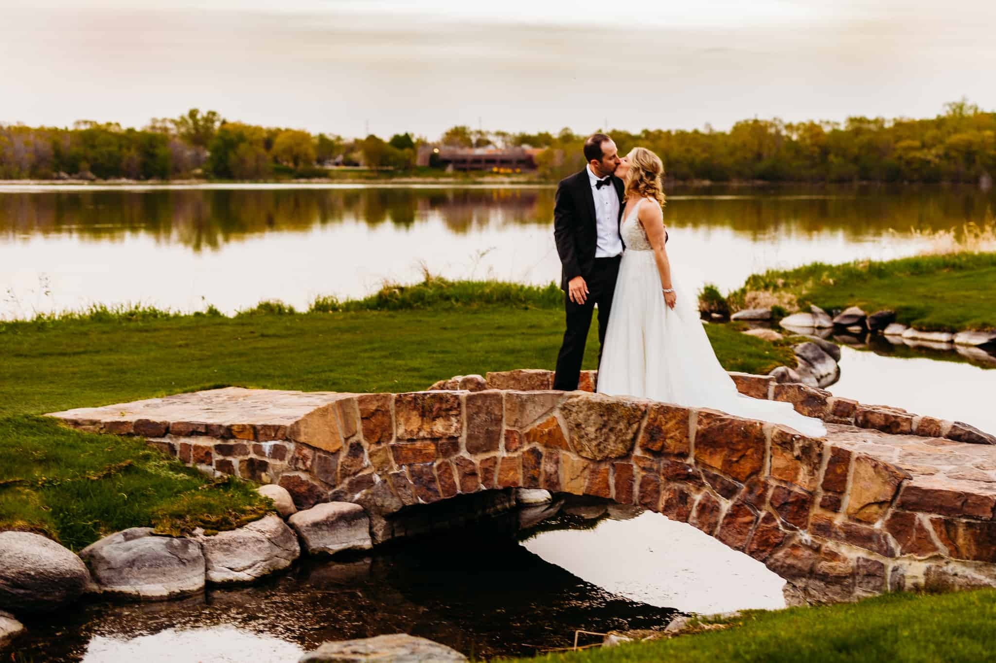 Photo of newly married husband and wife kissing at their Hazeltine National Golf Club Wedding