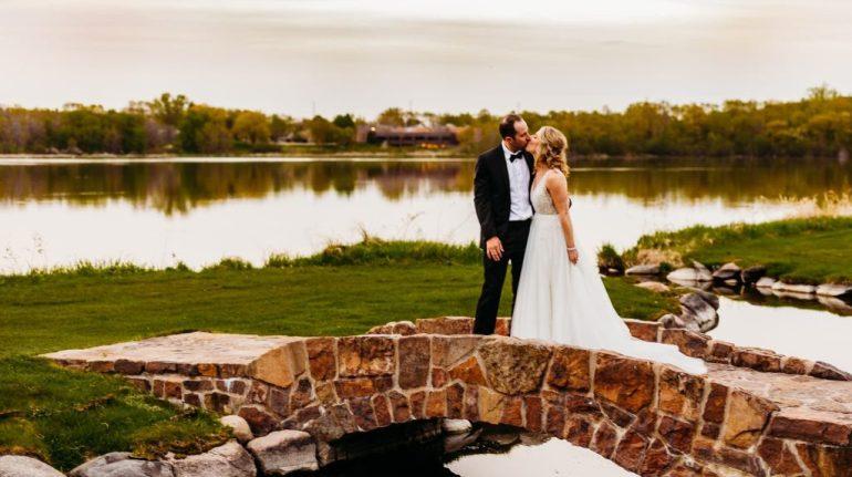 Minneapolis wedding photographer captures couple on bridge over stream at golf course wedding