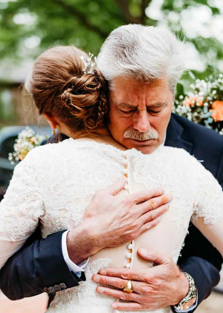 Bride's father hugs her at her Mill Race Village Wedding