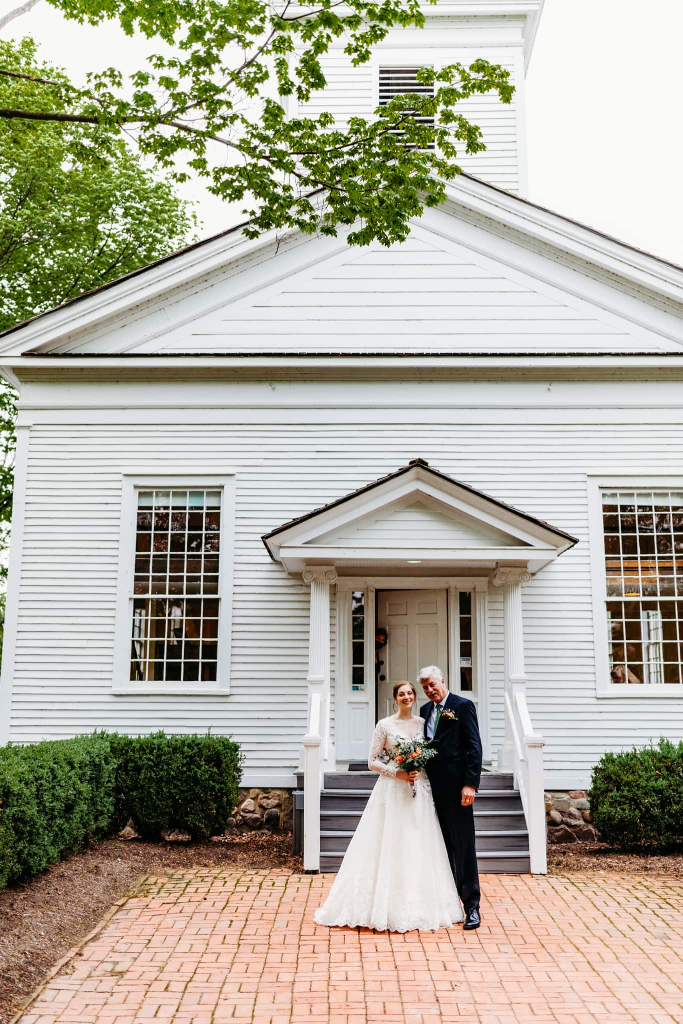 Bride and her dad pose outside of the chapel at Mill Race Village in northville, Michigan