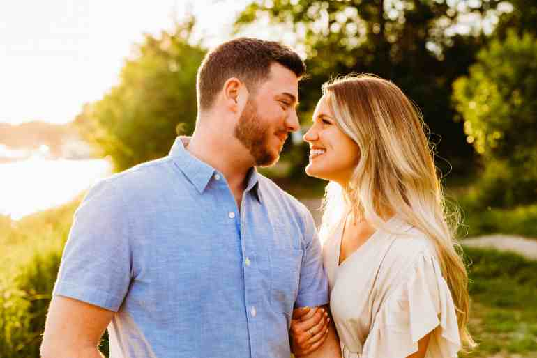 A couple looks at each other, touching noses, during a summer sunset engagement photo session