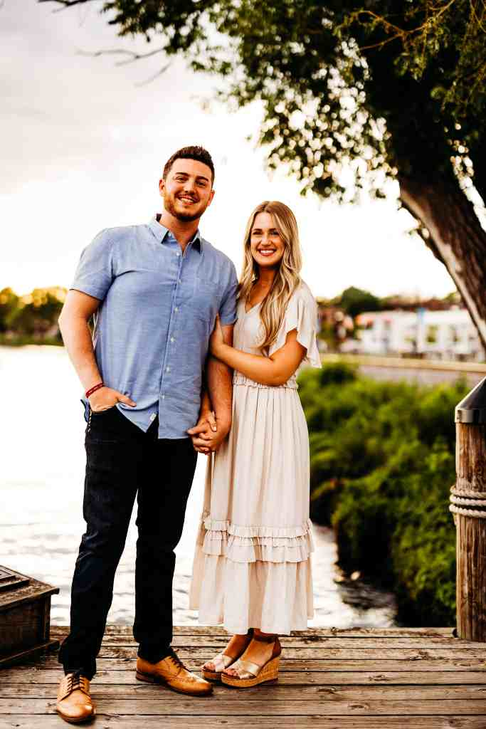 Couple stands together on a dock and smiles at the camera during their summer sunset engagement photo session