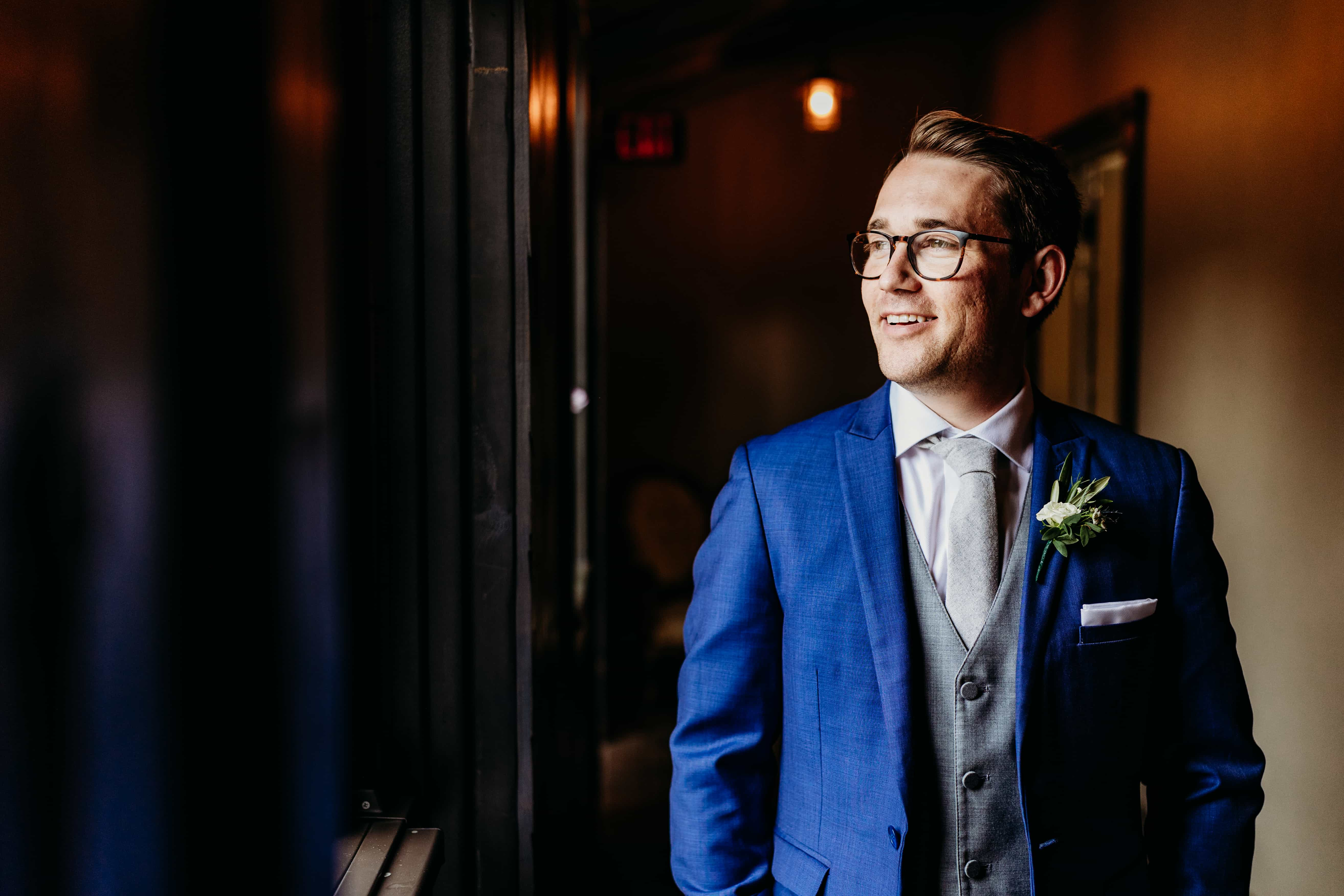 Groom smiles out the window at his Rolling Ridge wedding