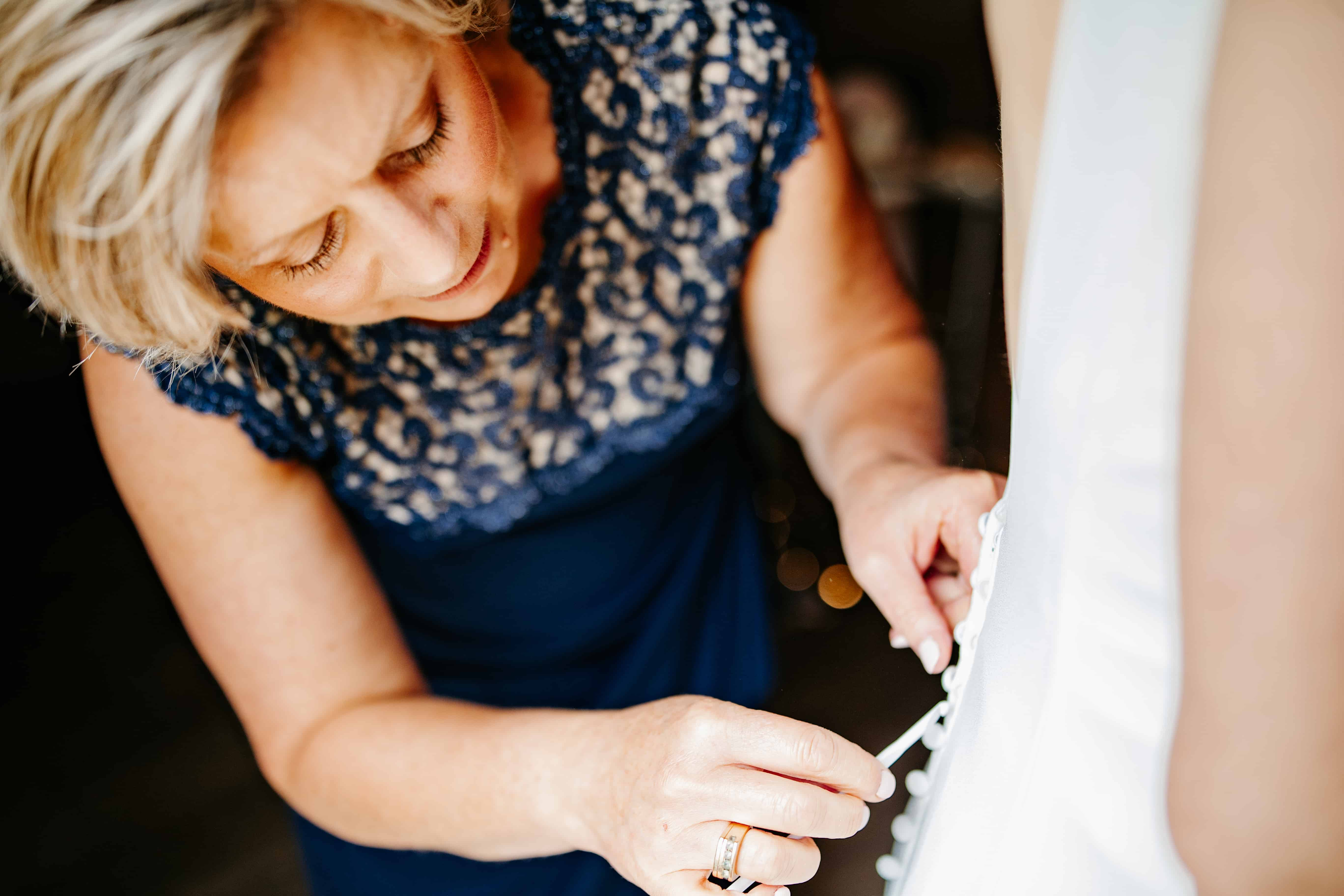 Mom buttons up bride's dress before her Rolling Ridge Wedding