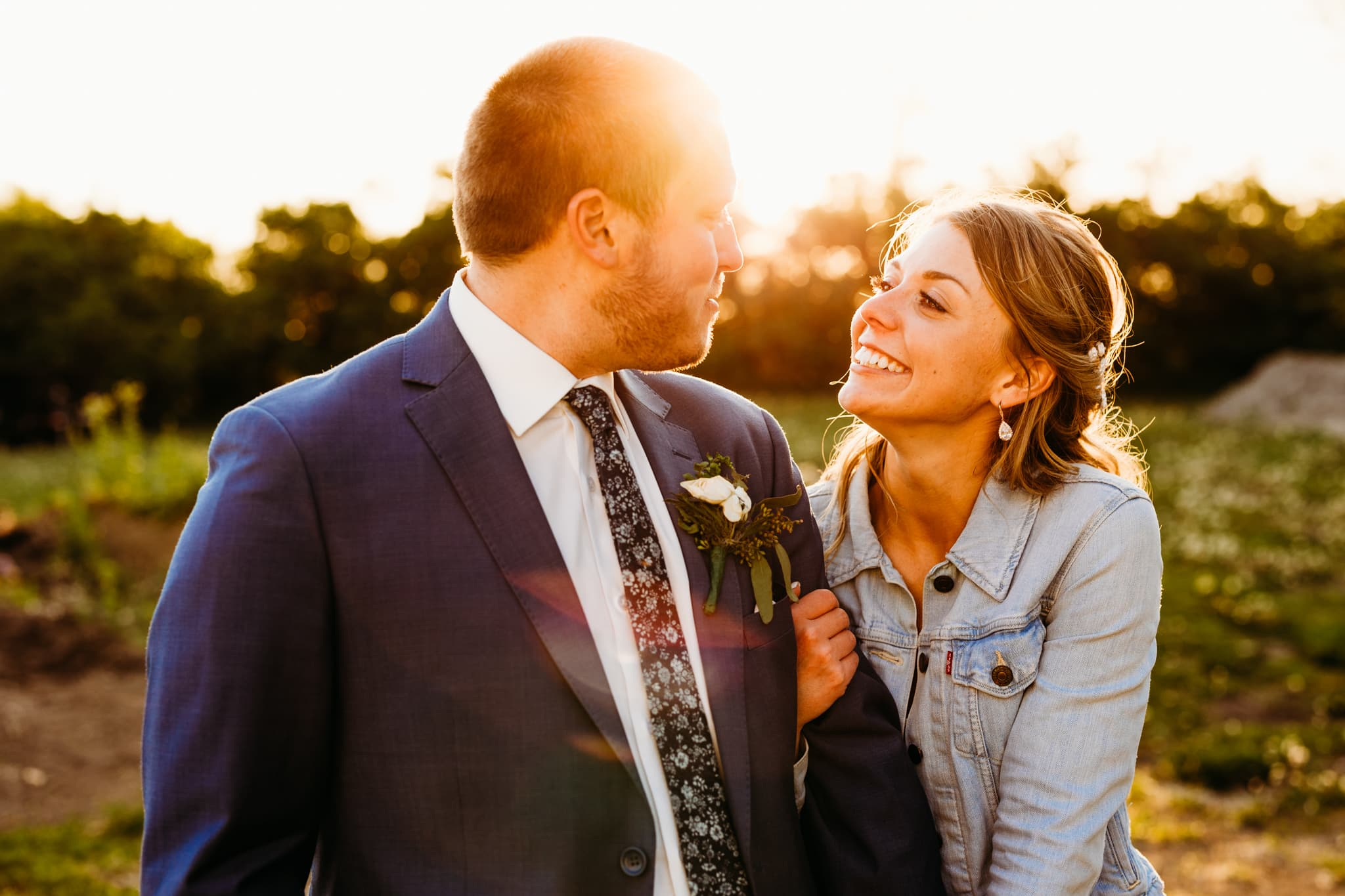 Couples smiles at each other outside at their Schroeder Farms wedding