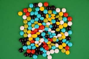 Multicolored round candies on green background