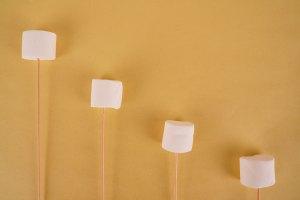 White marshmallows with sticks on yellow background