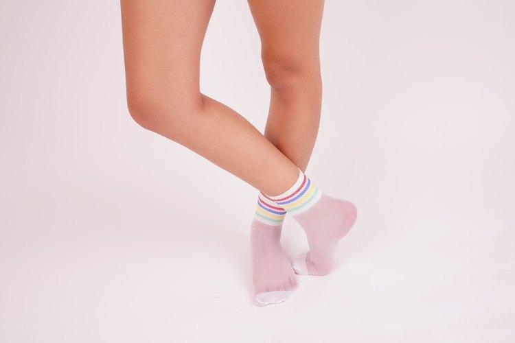 Female legs in white socks in the studio