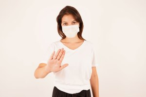 Girl in medical mask making stop gesture