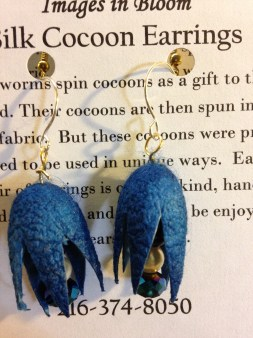 Silk cocoons dyed blue and cropped to have petal points. Suspended from the center is a dangle of czech glass sparkles.