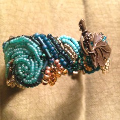 shades of blues and gold/copper swirls make up a dense mat of pattern for this bracelet