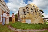 "20000104 CTY Volunteer workers and vistors to the Hawaii Okinawa Cneter visit this 18 ton rock that was brought over from Okinawa. Inscribed is ""Let's set out into world. Our home is the Five Continents. With sincere forth and determination. Remembering the marble stone of Kin."" PHOTO BY DENNIS ODA. JAN. 4, 2000. FRAME #5020."