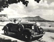 1935 Chevrolet convertible with Diamond Head and Waikiki Beach in the background