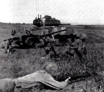 A bazooka team on maneuvers with a camouflage-painted M4 Sherman tank
