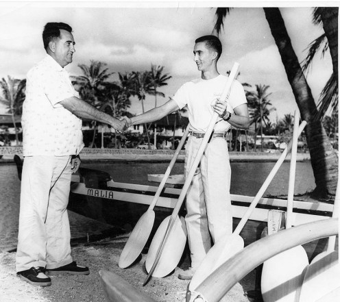 Abel Gomes shaking hands with another man alongside the Waikiki Surf Club's canoe, Malia-IanLind