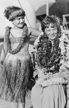 Flower leis drape Amelia Earhart in Honolulu on January 3, 1935-NatlGeographic