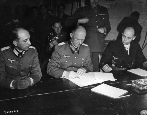 General Alfred Jodl (1890 - 1946) Hitler's military advisor, controller of German High Command and chief of the Operations Staff (centre), signs the document of surrender (German Capitulation) of the German armed forces at Reims in General Eisenhower's headquarters. He is joined by Major Wilhelm Oxenius (left) and Hans Georg von Friedeburg, Admiral of the Fleet (right). Original Publication: People Disc - HF0475 (Photo by Keystone/Getty Images)