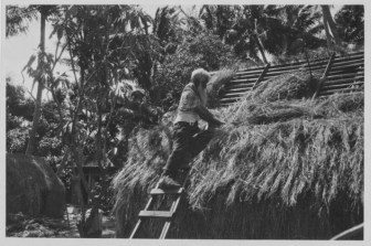 Hawaiian man thatching a grass house at Lalani Village, Waikiki-PP-32-3-004-1930s