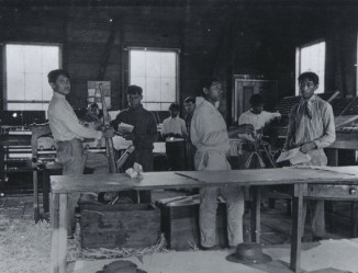 Lahainaluna_seminary_workshop,_mechanical_printing_press_and_movable_type_in_type_case_in_background,_ca._1895