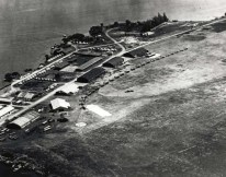 Luke Field on Ford Island with DH-4 and JN-4/6 aircraft lined up. At lower left are aircraft packing crates. Round spot on field is compass rose.