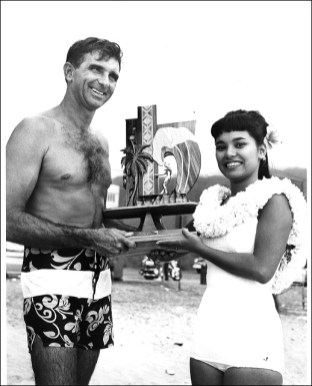 Makaha International Surfing Championships, 1965. George Downing, 1st place winner, Senior Men's Division, receiving trophy from Queen Leimomi. Photographer unknown.